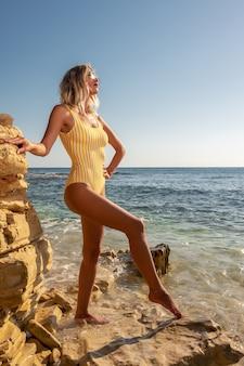 Schitterende mannequin op een tropisch rotsachtig strand