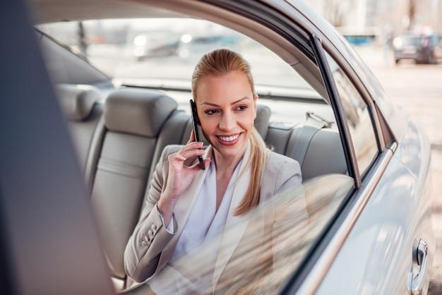 Schitterende onderneemster die smartphone in de auto gebruiken.