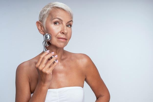 Schitterende rijpe vrouw die witte beha draagt die een metalen gezichtsmassageapparaat gebruikt