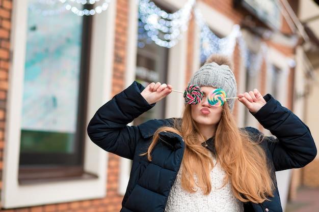 Schitterende roodharige jonge vrouw die een grijze gebreide muts draagt en kleurrijke kerstsnoepjes vasthoudt bij de etalage