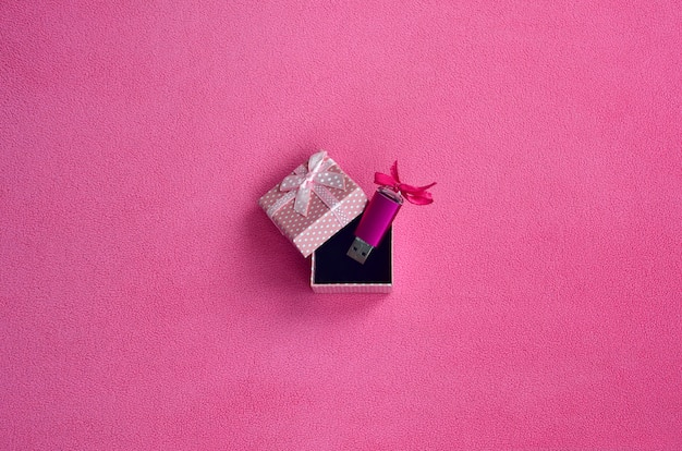 Schitterende roze usb-flashgeheugenkaart met een roze strikje ligt in een klein geschenkdoosje in roze