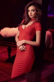 Schitterende schoonheids jonge donkerbruine vrouw die rode kleding draagt