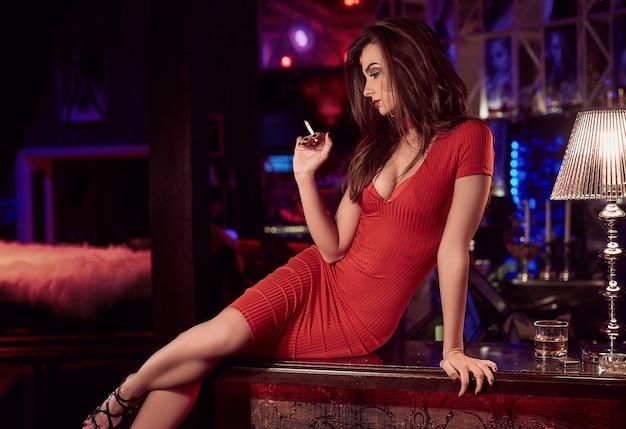 Schitterende schoonheids jonge donkerbruine vrouw in rode kleding met sigaret en whisky