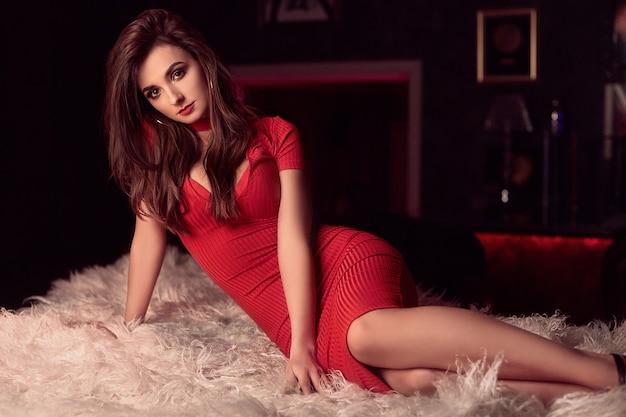 Schitterende schoonheids jonge donkerbruine vrouw in rode kleding op een wit bont