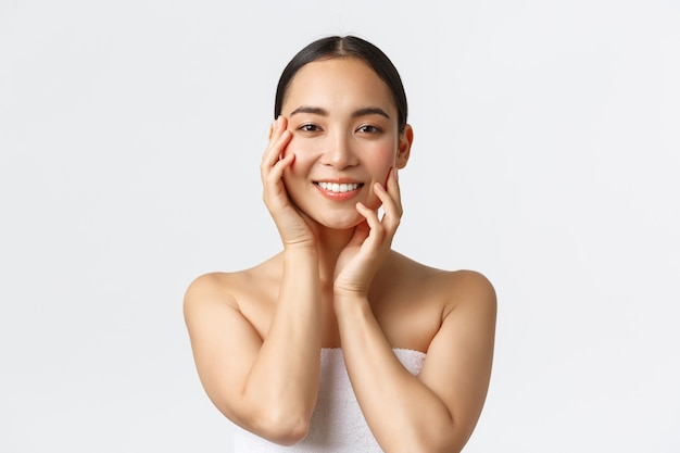 Schitterende sensuele aziatische vrouw in handdoek die gezicht aanraakt en glimlacht, huidverzorgingsproducten toepast, cosmetische procedure in de spa salon, gezicht masseert en camera blije, witte achtergrond starend.