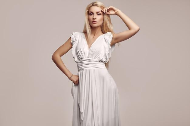 Schitterende sensuele blondevrouw in manier antieke witte kleding