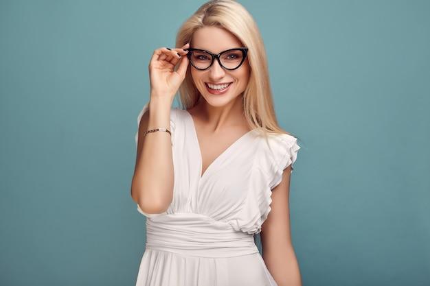 Schitterende sensuele blondevrouw in manier witte kleding