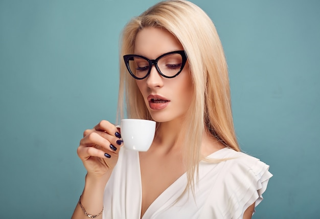 Schitterende sensuele blondevrouw in witte kleding met kop van koffie