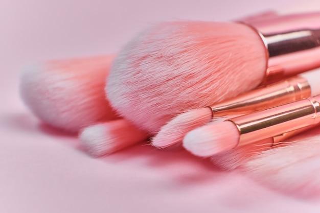 Schitterende set professionele donzige roze make-up kwasten op een roze ondergrond. detailopname. selectieve zachte focus