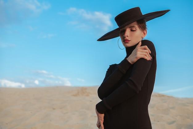 Schitterende sexy vrouw die op het zand in de woestijn danst