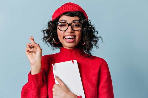 Schitterende student die met tandsteunen notitieboekje houdt