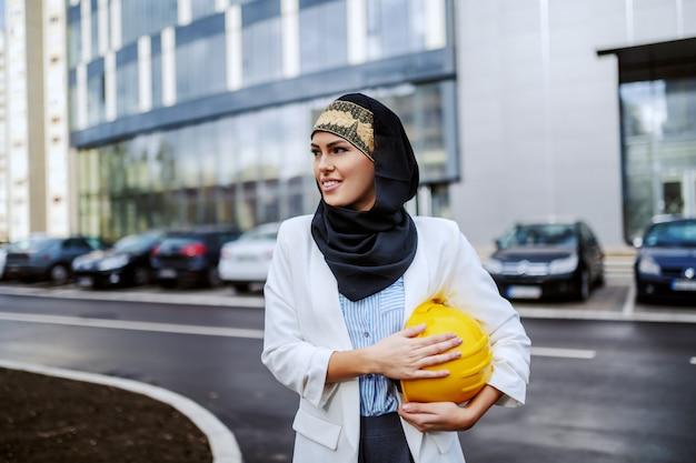 Schitterende succesvolle glimlachende positieve vrouwelijke moslimarchitect die voor haar firma met helm onder oksel staat.