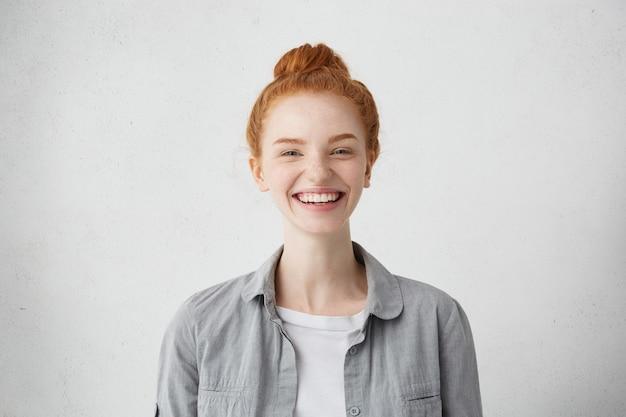 Schitterende tevreden dame die haar rood haar in knoop draagt en met opwinding in camera kijkt