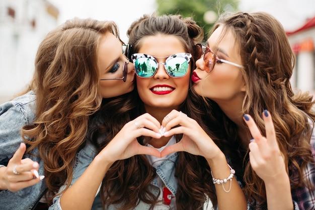 Schitterende tieners die in zonnebril hun vriend kussen die bij camera met hartgebaar glimlachen.