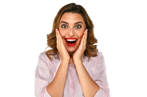 Schitterende verraste gelukkige, glimlachende vrouw met witte tanden, rode lippen grote ogen