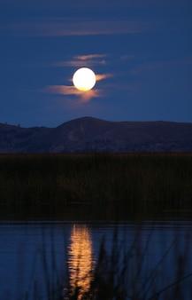Schitterende volle maanmening van drijvende eilanden uros op meer titicaca, puno, peru, zuid-amerika