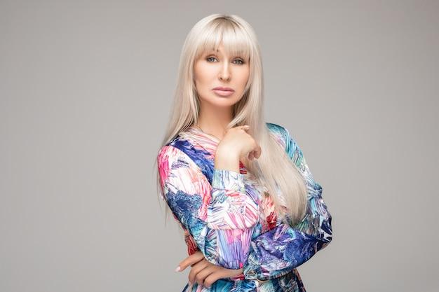 Schitterende volwassen blonde vrouw in kleurrijke blouse.