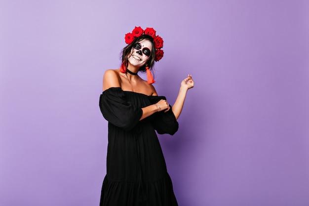 Schitterende volwassen dame in zwarte sundress die op geïsoleerde muur danst. meisje met rozen in zwart haar lacht