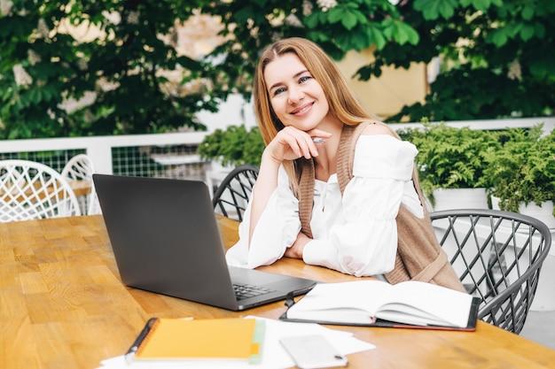 Schitterende volwassen vrouw die thuis aan de computer werkt en glimlachend naar de voorkant kijkt