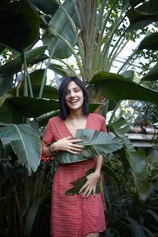 Schitterende vriendelijk ogende donkerharige jongedame in rode jurk met witte strepen die zich vermaakt in de plantenkwekerij, haar lichaam bedekt met twee grote groene bladeren, vrolijk lachend. verticaal schot