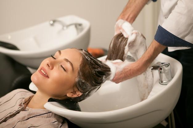 Schitterende vrouw die haar haar heeft dat door kapper wordt gewassen