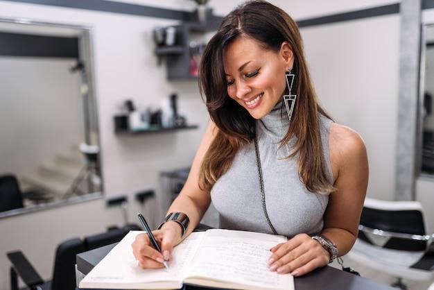 Schitterende vrouw die in gast schrijft of commentarenboek in de schoonheidssalon.