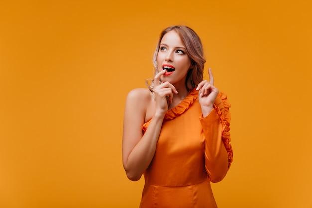 Schitterende vrouw die in oranje kleding verbazing uitdrukt
