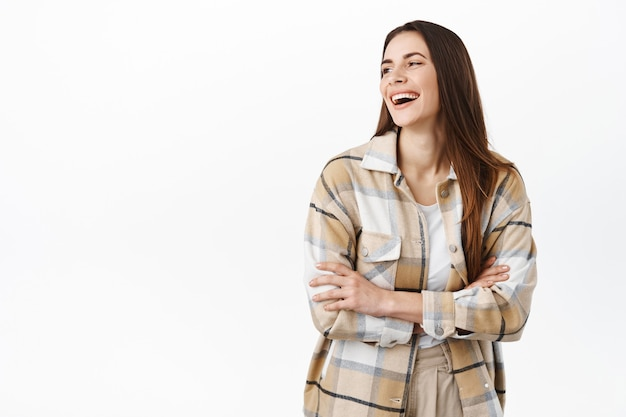 Schitterende vrouw die lacht, opzij kijkt naar de promotekst van de kopieerruimte met een tevreden glimlach, staande in een geruit overhemd over een witte muur