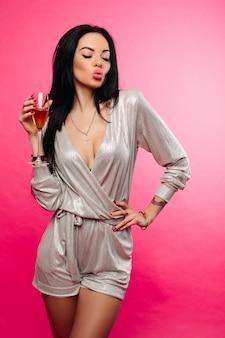 Schitterende vrouw die met fluit van champagne luchtkus met gesloten ogen maken.