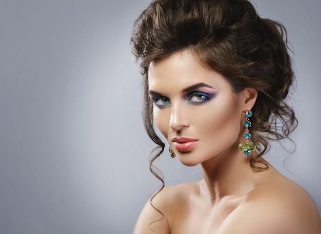Schitterende vrouw die mooie dure oorringen met juwelen draagt