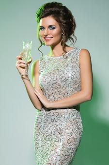 Schitterende vrouw die mooie kleding met een glas champagne draagt