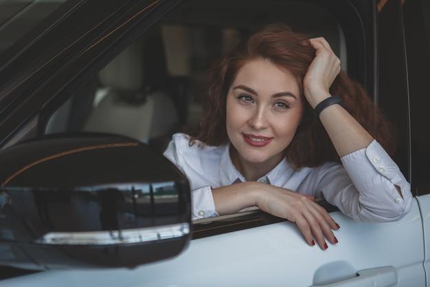 Schitterende vrouw die nieuwe auto koopt bij het handel drijven