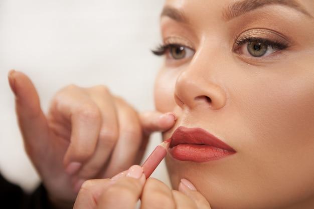 Schitterende vrouw die professionele make-up krijgt