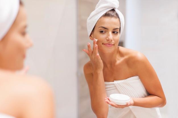 Schitterende vrouw die vochtinbrengende crème op gezicht toepast
