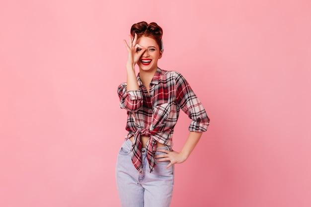 Schitterende vrouw in jeans die ok teken toont. lachend pinup meisje gebaren op roze ruimte.