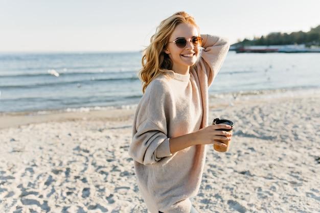 Schitterende vrouw in sweater die zich op zeekust bevindt. fashiinable blonde vrouw die van thee geniet dichtbij oceaan.