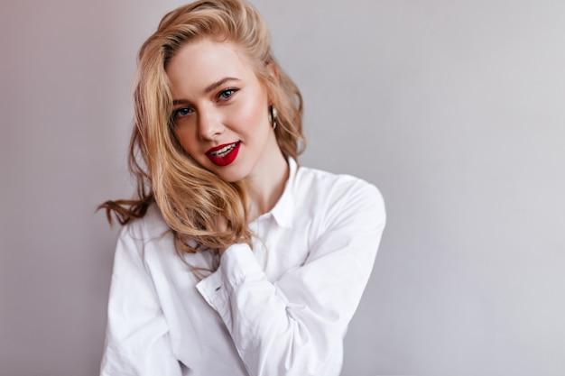 Schitterende vrouw in wit overhemd. glamoureuze blonde meisje poseren op lichte muur.