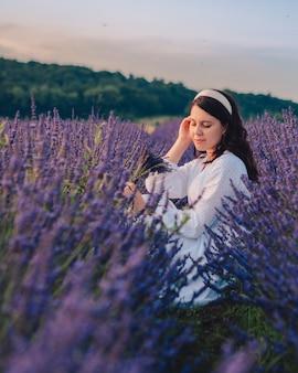 Schitterende vrouw in witte jurk bij zonsondergang in het lavendelveld