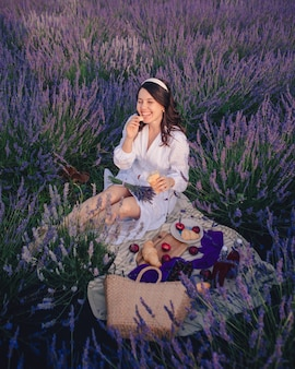 Schitterende vrouw in witte jurk op lavendelveld met picknick