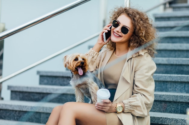 Schitterende vrouw met krullend haar in modieuze kleding zit met haar hond in de stad en spreekt via de telefoon.
