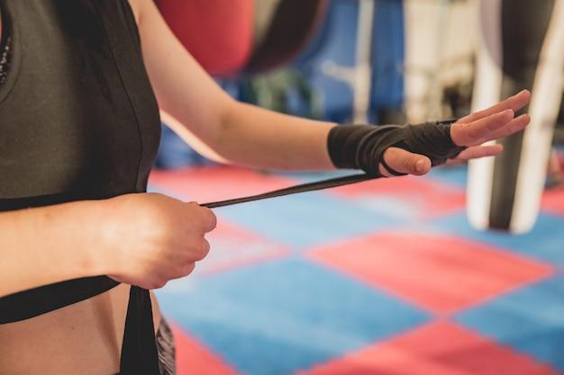 Schitterende vrouw, mma vechter in gymnastiek tijdens opleiding. voorbereiding op een wedstrijd met harde kooien