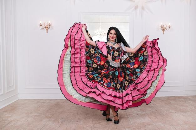 Schitterende vrouw, voert een snelle zigeunerdans uit. foto met ruimte voor tekst