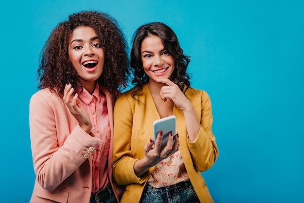 Schitterende vrouwen poseren met telefoon