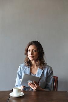 Schitterende vrouwenzitting die binnen tabletcomputer met behulp van.