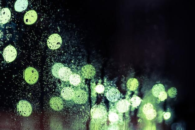 Schittering van de nachtstad door het raam in de regendruppels