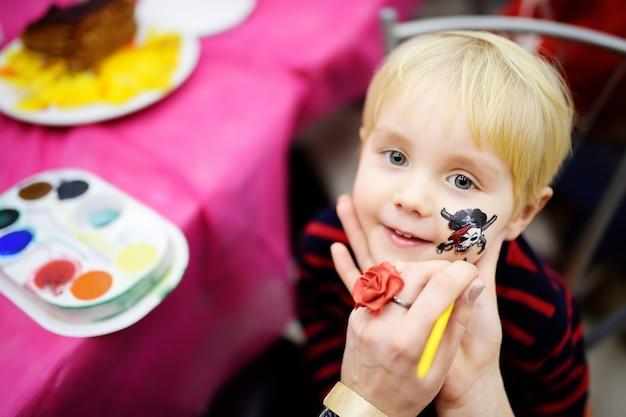 Schminken voor schattige kleine jongen tijdens kinderen verjaardagsfeestje