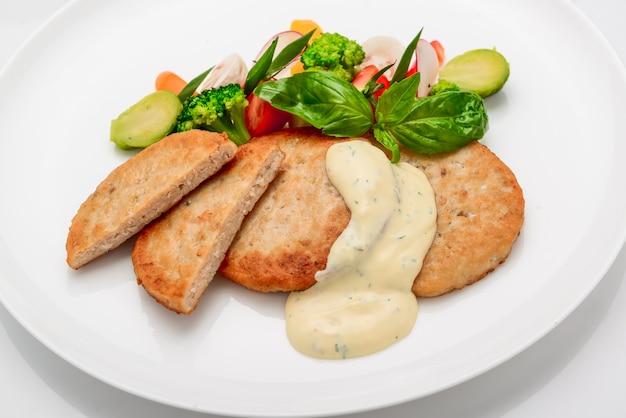 Schnitzel, kipkotelet met witte saus en groenten