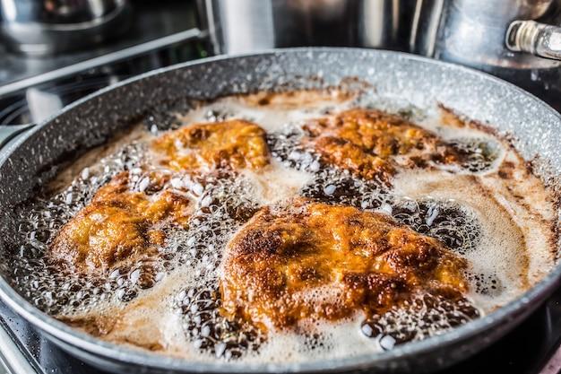 Schnitzels worden gebakken in olie in een donkere pan.
