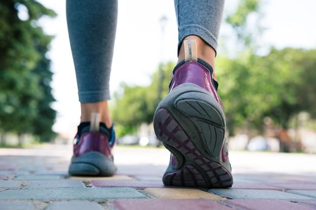 Schoeisel op vrouwelijke voeten die op weg lopen