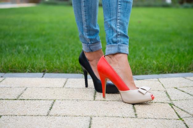 Schoeiselmode, stijl. benen in schoenen en jeans op groene grasachtergrond. keuze, concept kiezen. hoge hakken van verschillende leerkleur op vrouwelijke voeten. winkelen, verkoop, aankoop.